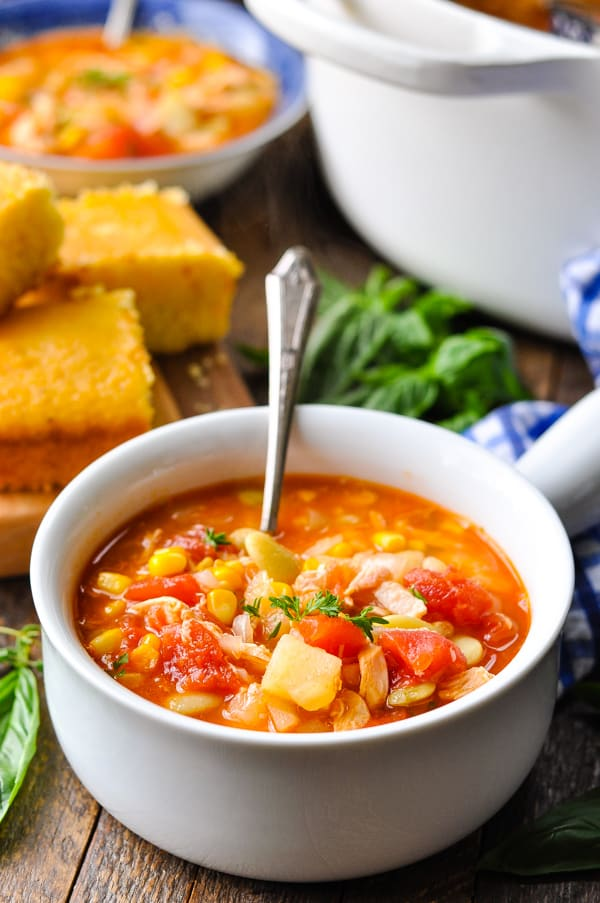 An easy brunswick stew recipe served in a white soup bowl on a wooden table