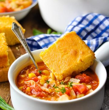 Chicken brunswick stew in a white bowl with a side of cornbread