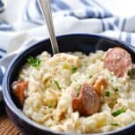 Close up front shot of a spoon in a bowl of chicken bog with smoked sausage