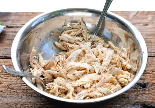 Shredded chicken in a metal mixing bowl