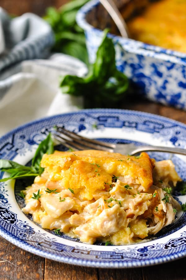 Front shot of chicken and cornbread casserole served on a blue and white plate with fresh parsley garnish
