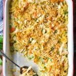 Overhead shot of chicken noodle casserole in a white baking dish with a silver serving spoon