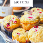 Front shot of a bowl full of cranberry muffins with text title box at the top