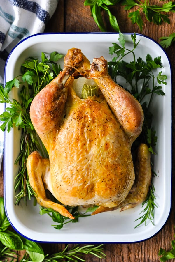 Overhead shot of a whole chicken in a white dish with blue trim and crispy golden brown skin