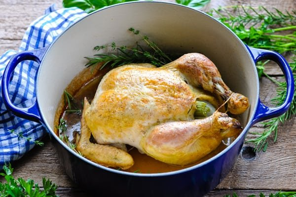 Horizontal shot of a whole roasted chicken in a Dutch oven