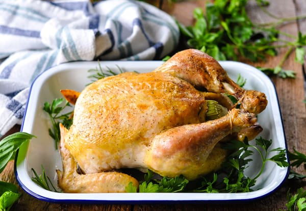 Horizontal shot of a whole roast chicken on a white serving platter with fresh herbs