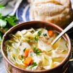 Easy chicken noodle soup in a copper bowl with fresh parsley garnish