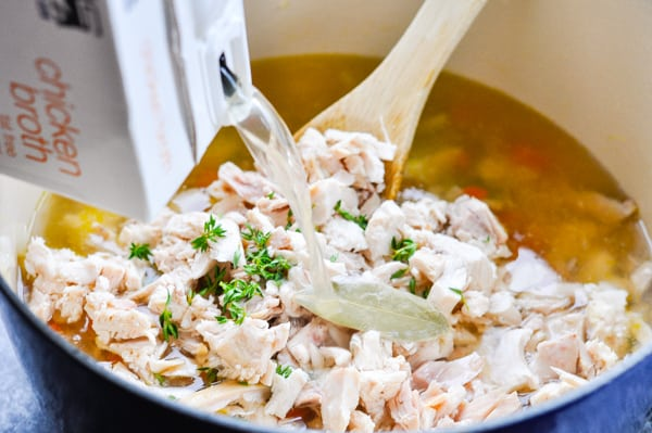 Adding broth to a pot of chicken soup