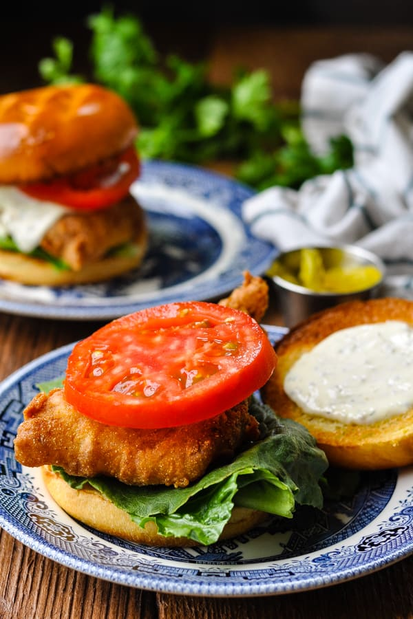 Crispy fried fish sandwich open face with tomato and tartar sauce