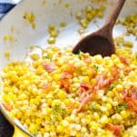 Close up front shot of fried corn with bacon in a cast iron skillet with a wooden spoon