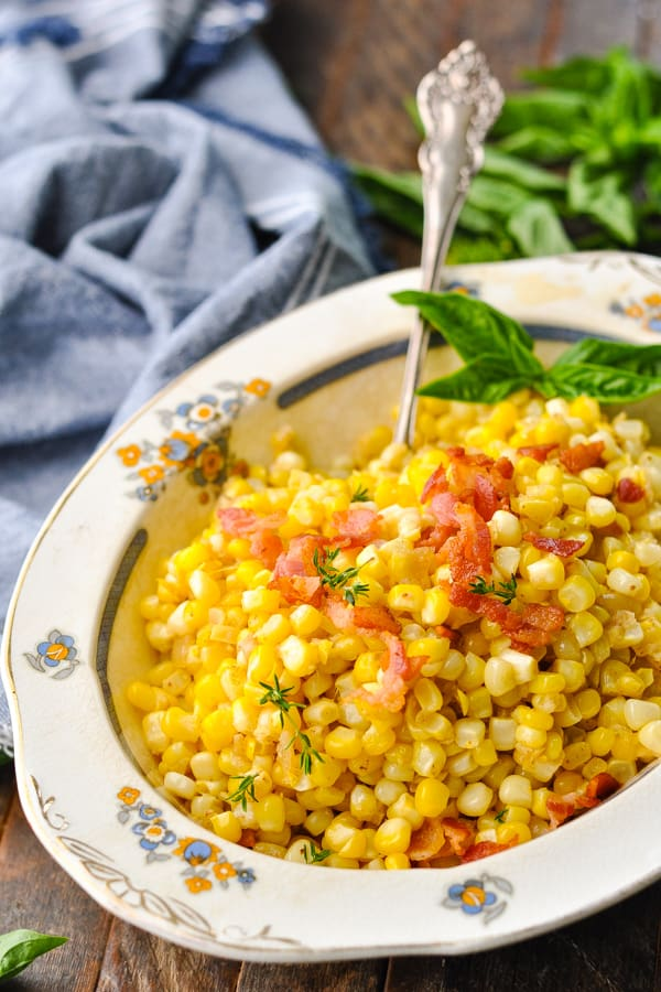 Front shot of a bowl of fried corn topped with bacon and fresh basil