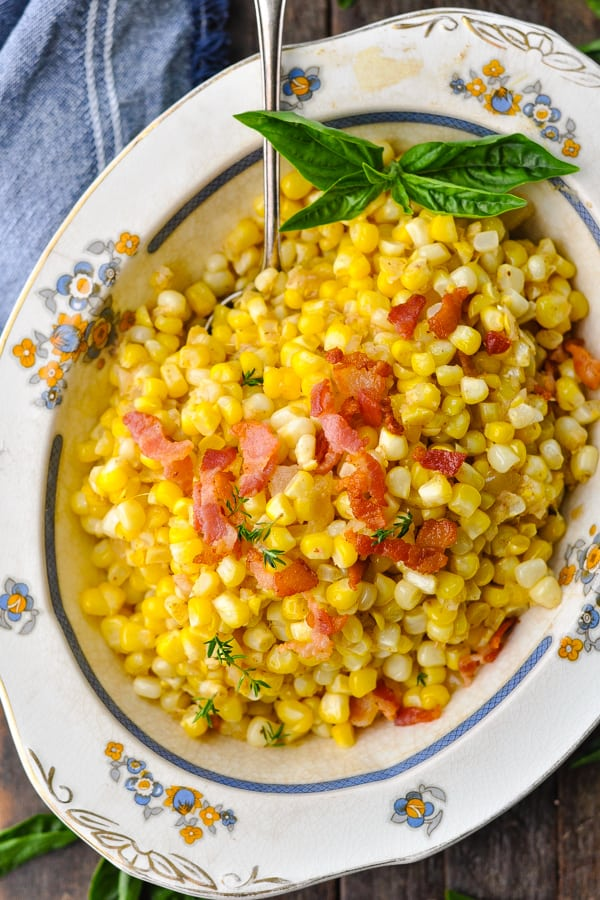 Overhead image of southern fried corn with bacon in a bowl with a silver serving spoon