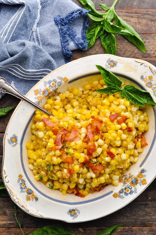Overhead image of skillet fried corn served in a vintage bowl on a wooden table
