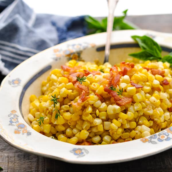 Bowl of skillet fried corn with bacon and fresh herbs