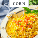 Close up side shot of skillet fried corn in a serving bowl with text title box at the top
