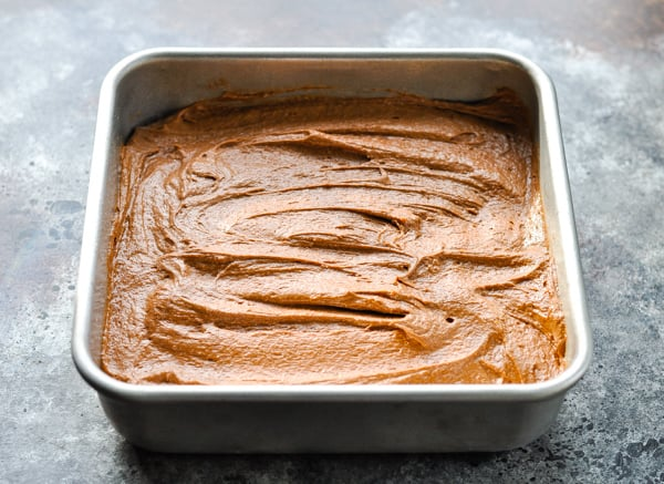 Brownie batter spread in a square baking dish