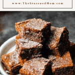 Most fudge brownies on a platter with text title box at the top
