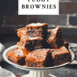 Front shot of fudgy brownies on a white serving tray with text title box at the top