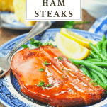 Slice of glazed ham steak on a plate with green beans and a text title at the top