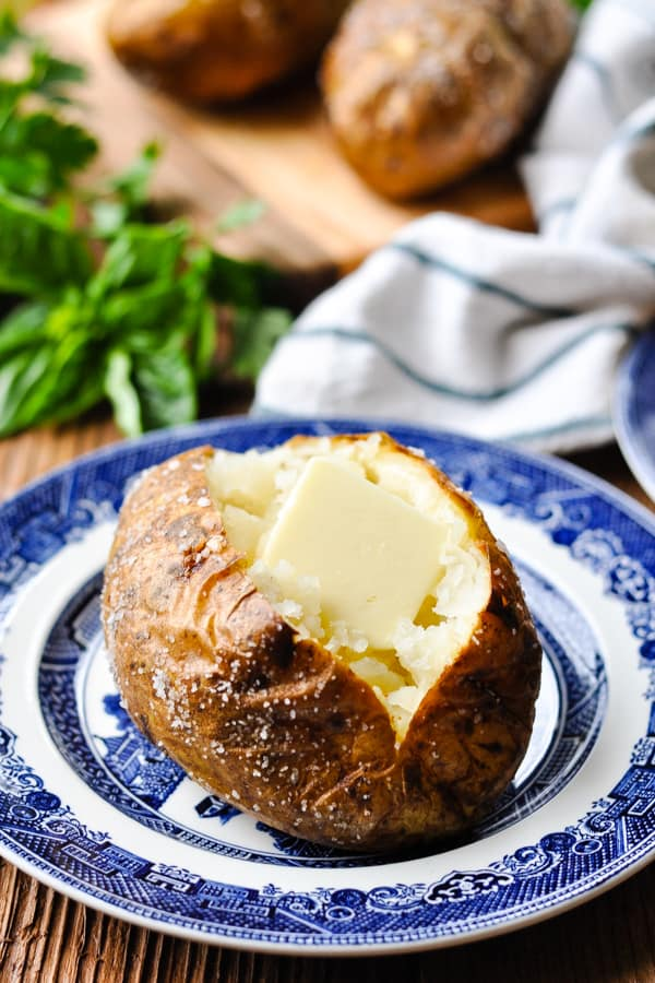 Front shot of an oven baked potato with a pat of butter