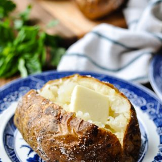 Open baked potato with salt and butter on a blue and white plate