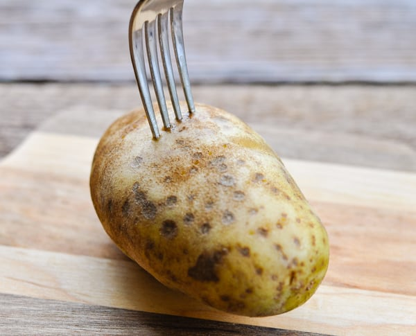 Using a fork to poke holes in a potato