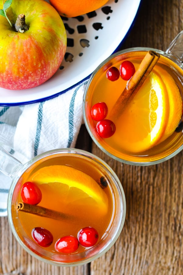 Overhead shot of two glass mugs of mulled cider on a wooden table