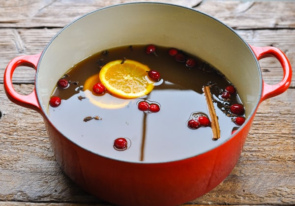 Process shot of making mulled cider in a red dutch oven