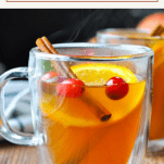 Close up front shot of a hot mug of mulled cider with a text title at the top