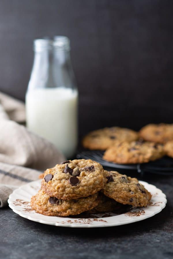 Side shot of old fashioned oatmeal chocolate chip cookies with milk in the background