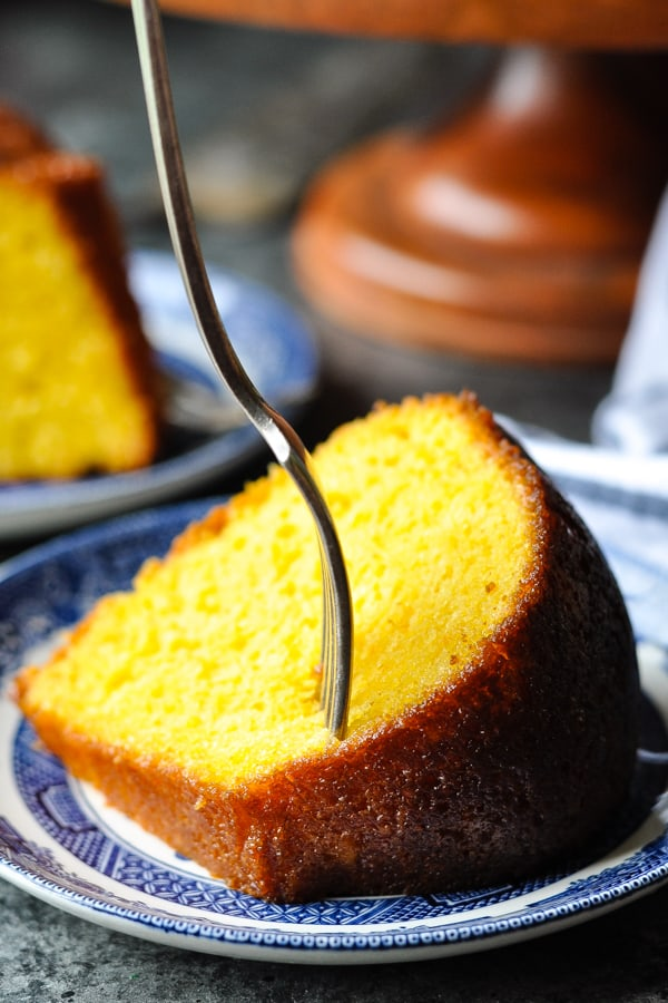 Close up shot of a fork digging into a slice of orange juice cake