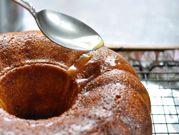 Spoon drizzling orange juice glaze over a bundt cake