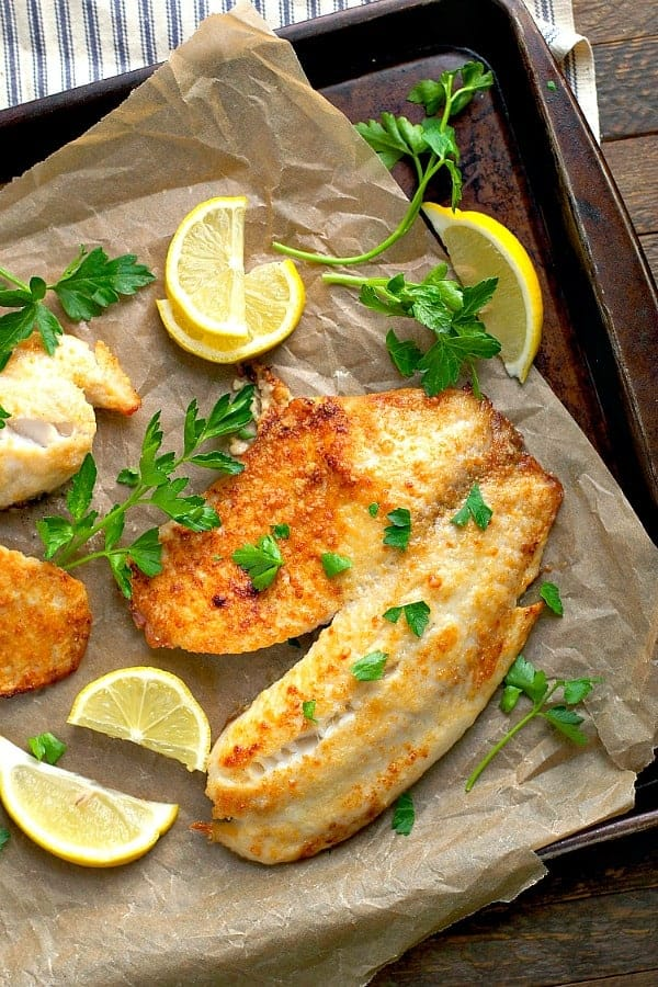 Overhead image of crispy golden brown parmesan crusted tilapia with lemon and garlic