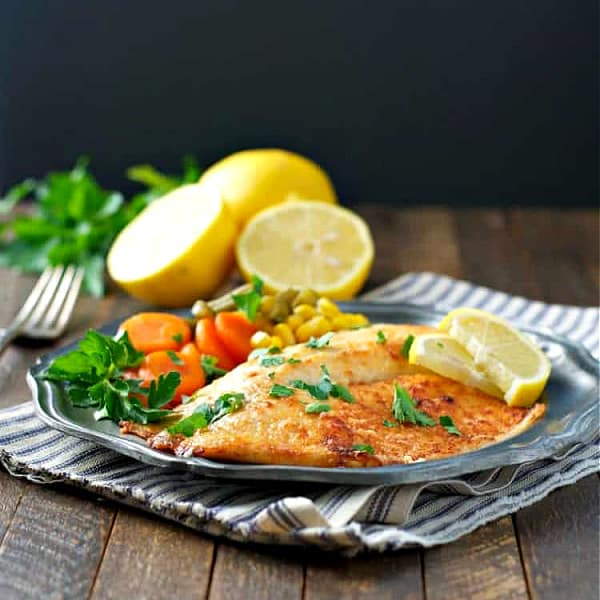 Side shot of parmesan crusted tilapia on a plate with lemon wedges