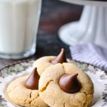 Close up side shot of three peanut butter blossom cookies on a small plate