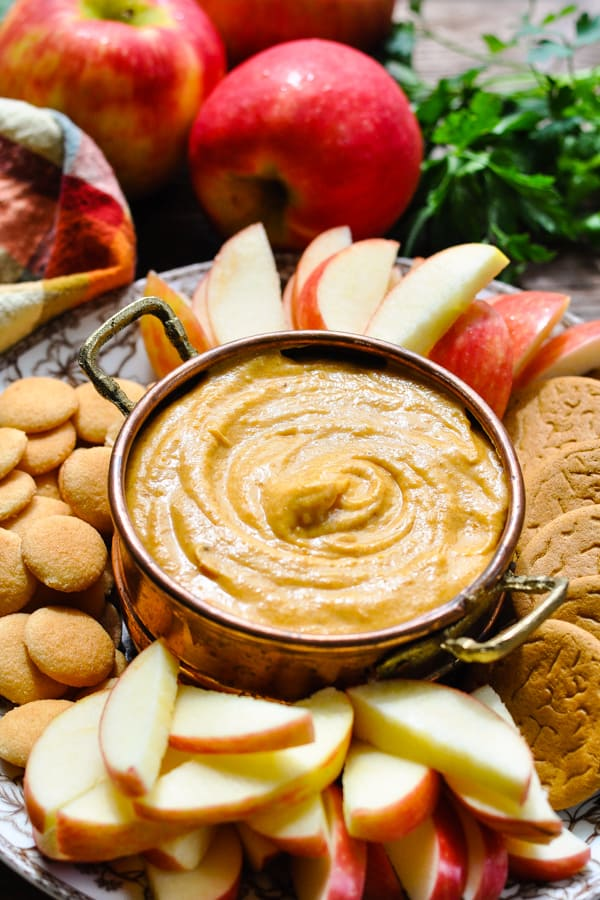 Front shot of a bowl of pumpkin cream cheese dip dessert with cookies and apples