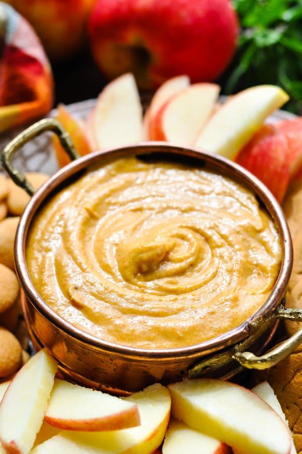 Close up side shot of a bowl of pumpkin dip for apples