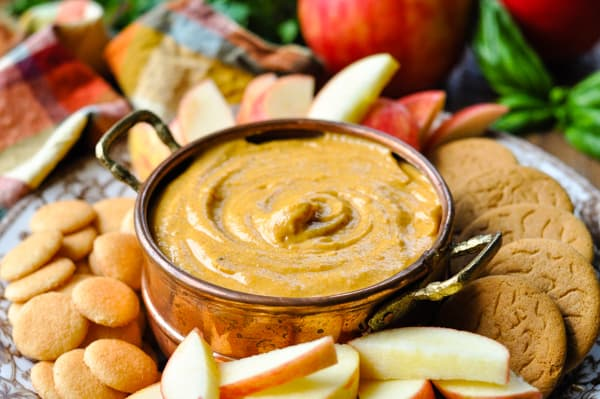 Horizontal shot of a tray of pumpkin dip and cookies and apples