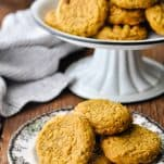 Front shot of a small plate of pumpkin oatmeal cookies with a cake stand in the background