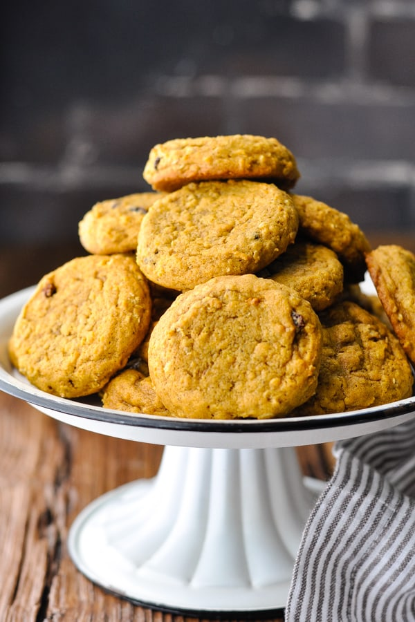 Front shot of pumpkin oatmeal cookies on a white cake stand with black trim