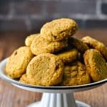 Tray piled high with old-fashioned soft pumpkin cookies in front of a dark brick wall