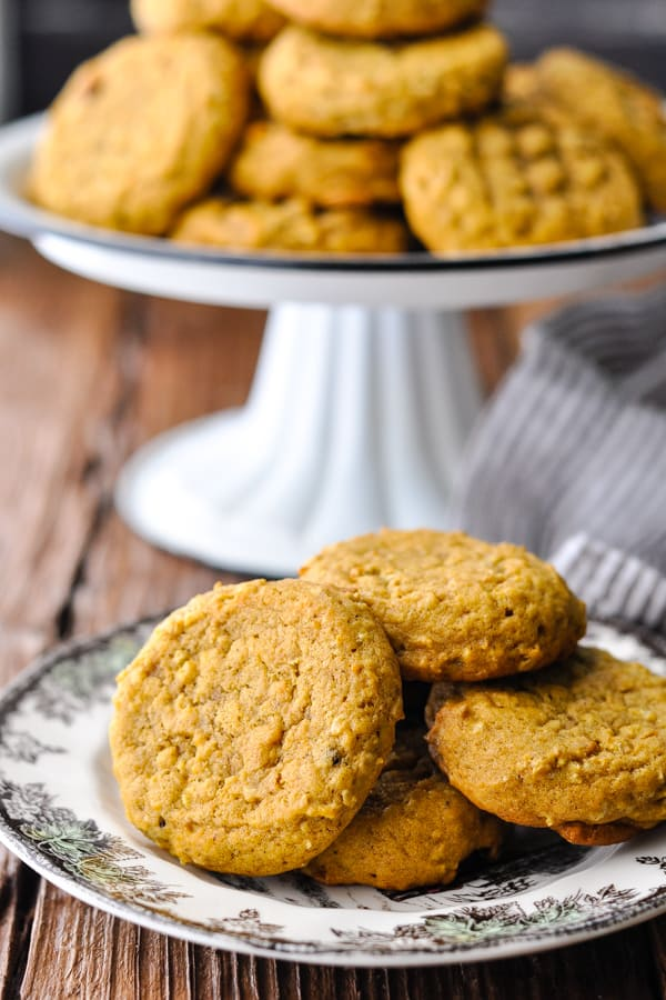 Plate of pumpkin cookies on a wooden table with cookie tray in the background