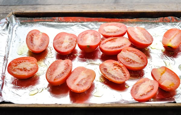 Halved roma tomatoes on a baking sheet