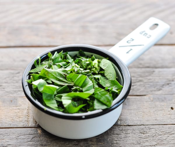 Chopped fresh basil in a measuring cup