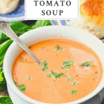 Basil on top of a bowl of roasted tomato basil soup with a text title box at the top