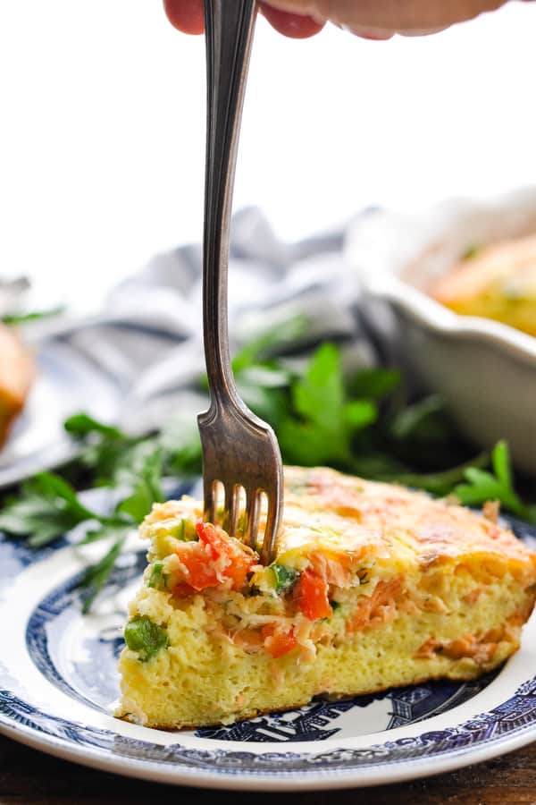Fork digging into a slice of crustless salmon quiche
