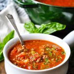 Silver spoon in a bowl of stuffed pepper soup with parsley on top