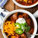 Overhead image of two bowls of texas chili with cheese sour cream and jalapenos
