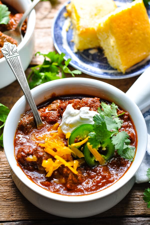 Close side shot of a bowl of Texas chili with toppings and cornbread in the background