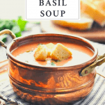Bowl of creamy tomato soup with croutons and fresh basil with a text title box at the top